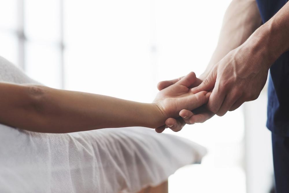 Fisioterapeuta a massajar mão de mulher com rizartrose ou artrose no dedo polegar