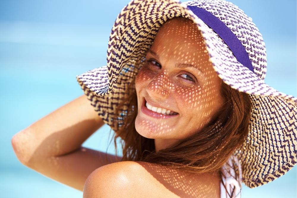 mulher com chapéu de abas largas, um dos vários cuidados a ter com o calor e aumento de temperaturas