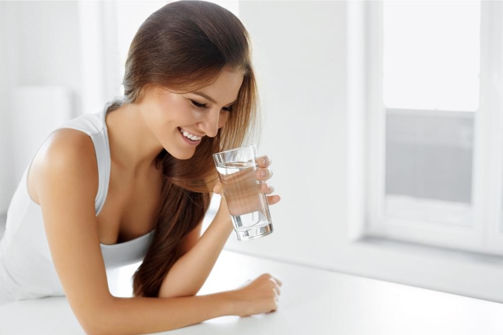 Mulher jovem no verão a beber água, porque é importante beber água sempre