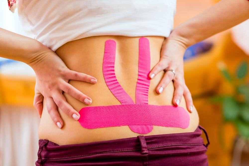 Mulher com dores nas costas e com bandas kinesio tape rosas aplicadas