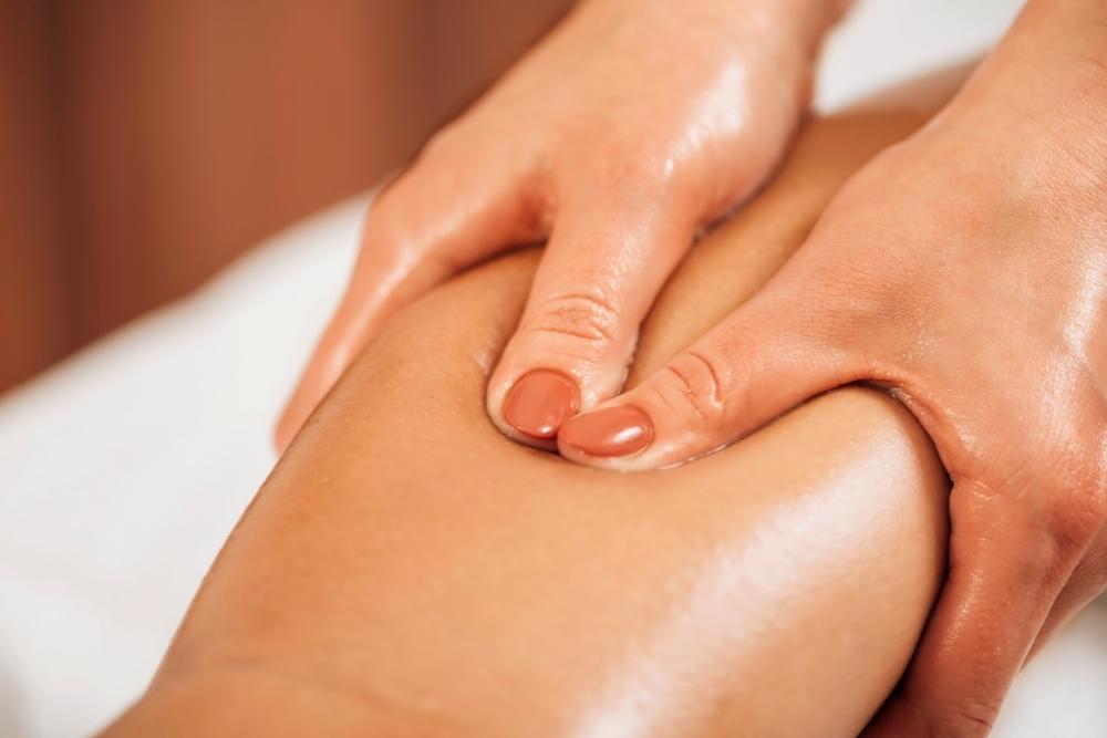 Fisioterapeuta a fazer drenagem linfática manual na perna de uma mulher